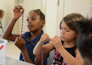 Two children hold up their unfinished beaded necklaces.