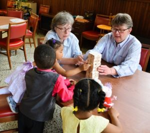 Sister Lynn Miller and Sandy Kiefer play jenga with their foster children.