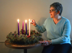 Associate Carla Gregory lighting a candle for the third week of Advent.