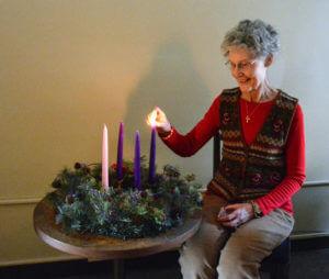 Associate Linda Biel lighting the first Advent candle.