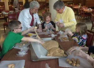 Sisters rolling bread dough with kindergartners